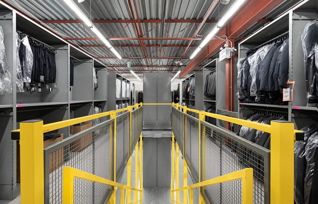distribution center for varied sku and order picking in steel shelving with catwalk, staircases, structural support for work station mezzanine