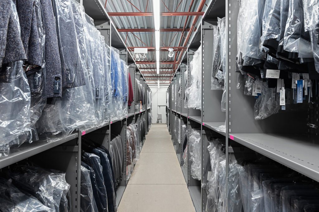 closed clip style shelving over catwalk with coat bar for clothing on hanger